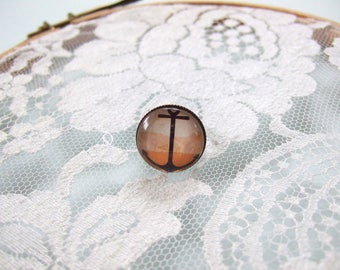 Round cabochon ring anchor on orange background