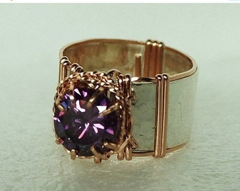Offering a 10mm round cut amethyst CZ set on a band of textured fine silver with 14K rose gold filled wire wrap. Size 10.5