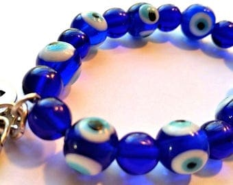 """Recovery bracelet: Blue Czech glass """"Evil Eye"""" beaded bracelet with silver-tone """"equality"""" charm and """"courage"""" charm--equal, healing"""