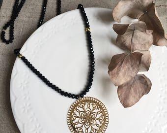 Sautoir Chloé avec perles facettées noires et estampe dorée