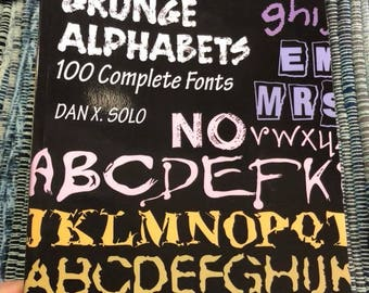 "Paperback Book ""Grunge Alphabets,"" 100 complicated fonts,  by Dan X. Solo.  Barely Opened."