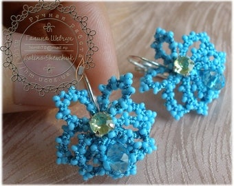 Little violet-shaped earrings are decorated with small crystals in the pith of flowers
