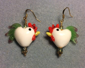 White with green tails heart shaped lampwork rooster bead earrings adorned with green Czech glass beads.