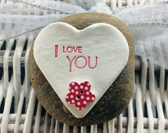 "Natural clay heart inscribed ""I love You"" with red dotty button mounted on a pebble"