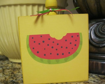 Summer Wood Block painted yellow with watermelon slice pictured on it.  Tied up with pink and green ribbons.