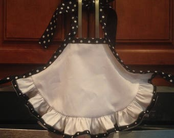 Baby apron full of polka dots! Adorable white apron with a variety of polka dot embellishments. A matching flower black n white headband.