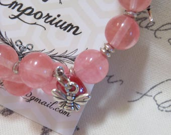 Pink glass beads with silver accents and a dangling bee charm memory wire bracelet