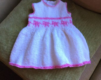 Hand knitted baby girl's summer dress in cotton decorated with a row of pink elephant