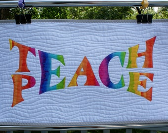 Teach Peace quilted wallhanging in rainbow colors