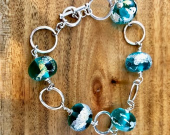 Stunning teal and silver beads with hand hammered sterling silver links, make this large bracelet a stunning addition for spring.