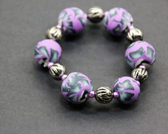 Bracelet of purple-grey beads on elastic.
