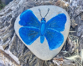 Blue butterfly hand painted on rock