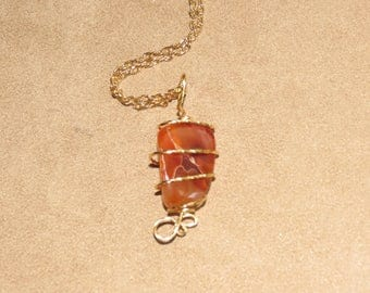 204 Caged wrapped Carnelian agate in gold
