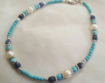 A simple delicate ocean themed gemstone beaded bracelet in blue hues featuring pearls