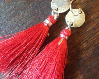 Red silk tassel earring on a silver hammered disc.