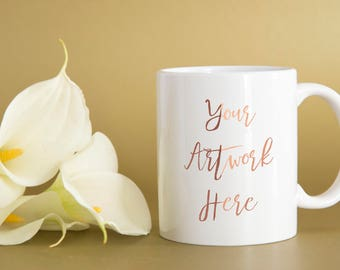 Calla lilies and white mug on a gold background