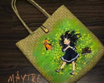 Little girl on straw bag