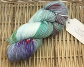 Variegated Fingering Weight Sock Yarn (75/25 Superwash Merino / Nylon) in greens, blues, and purples with fuschia speckles