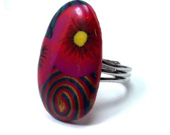 Elongated ring: a bright pink flower and a colorful spiral.
