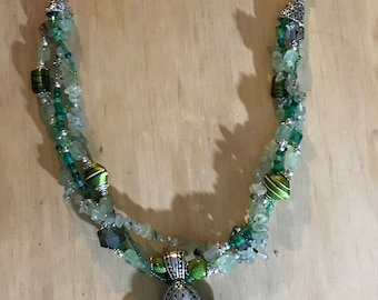 Green necklace, Peridot chipped rock and beads with green accent colored beads with a Fluer De Lis Pendant