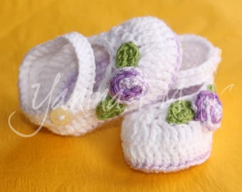 Strappy baby booties with a purple flower on the side