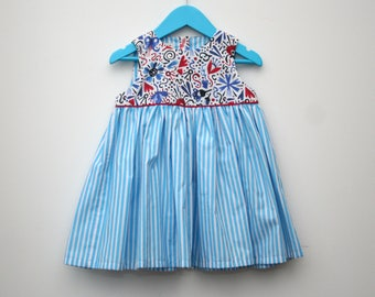 Toddler girls cute sleeveless dress, striped skirt, blue, white and red abstract print, birthday party outfit, cool dress for little girl.