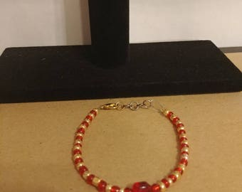 Red and gold tone beaded bracelet