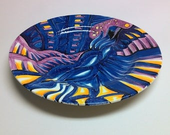 Hand painted round ceramic plate in blues, purples and oranges