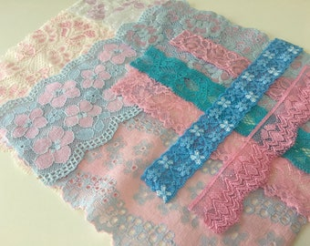 assortment of various smaller sheer lingerie tulle lace / mesh swatches — baby pink / light blue — different sizes and patterns