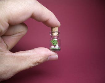 Tiny green tree and a family in a tiny bottle