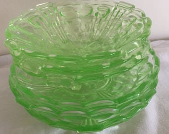 A set of six pieces of uranium/ vaseline glass; three small dishes, three shallow dishes/ saucers.