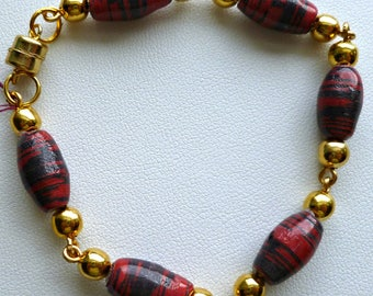 Red and black handcrafted paper bead bracelet with gold bead accents, magnetic closure