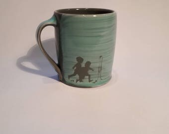 Decorated stoneware mug with kids and dinosaur
