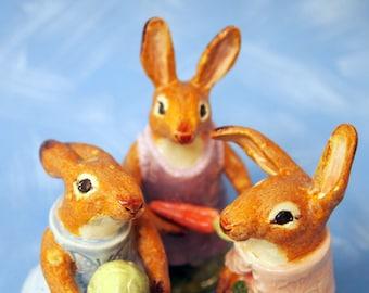 Three cute ceramic animal figurines rabbits with vegetables
