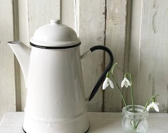 A vintage off white enamel coffee pot
