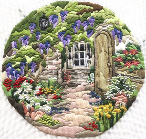 Completed embroidery on canvas, long stitched scene of beautiful garden with flowers and vines, circle, 11.5 inches / 29 cm across