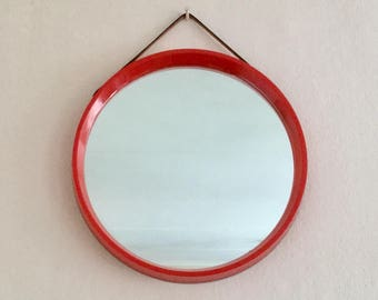 Small 1970's round retro red wall mirror with leather hanging strap. Made in Denmark.