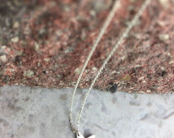 Delicate sterling silver star necklace embellished with a tiny light rose Swarovski crystal