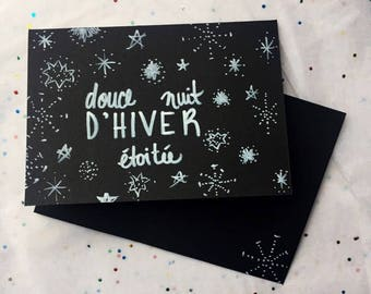 """Christmas card, white marker drawing of """" douce nuit d'hiver etoilé """" with stars on thick balck paper"""