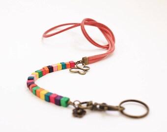 Cordon fantaisie multicolore avec cordon en simili cuir rose, perles en bois colorées et breloques