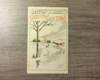 Vintage Christmas Greetings 1919 postcard feat. a snowy river scene with trees and a bridge, with postmark and 1-cent stamp