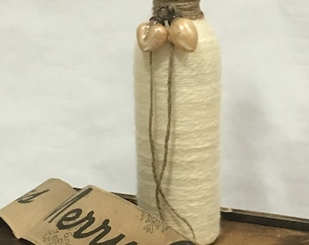 Rustic yarn-wrapped wine bottle with ornament accent.