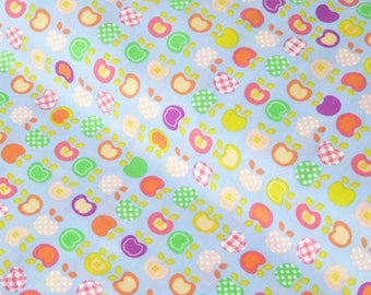 Apples to eat - fabric representing a multitude of small multi-colored apples on a light blue background