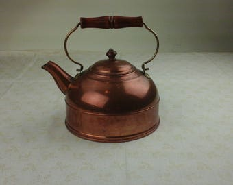 Vintage copper tea kettle with wood and brass handles.