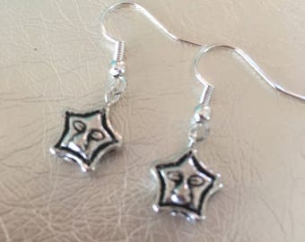 Silver earrings, silver dangle earrings, Silver star face earrings on a silver ear wire.