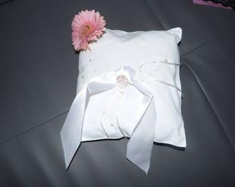 A white satin ring pillow