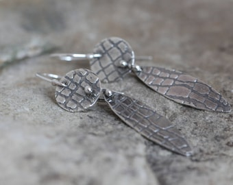 sterling silver disc and pod shaped earrings. fine silver barbell connections. textured. oxidized.