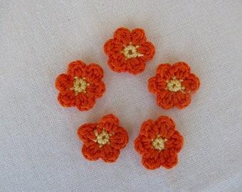 5 small orange crochet flowers