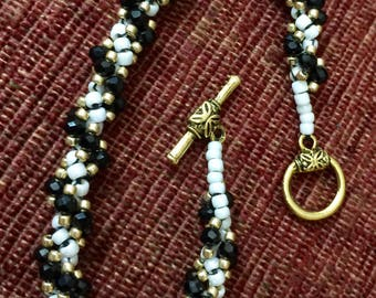 Classy  black faceted seed beads with a gold tone