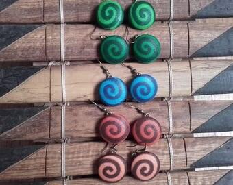 a pair of spiral earrings in wax
